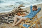 boční pohled na mladíka spočívající v plážové lehátko na písečné pláži