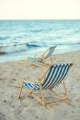Selektivní fokus dřevěných plážových lehátek na písečné pláži s mořem v pozadí