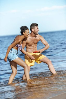 young multicultural couple playing with flying disc on beach on summer day