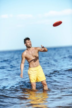 young man throwing flying disc while standing in sea on summer day