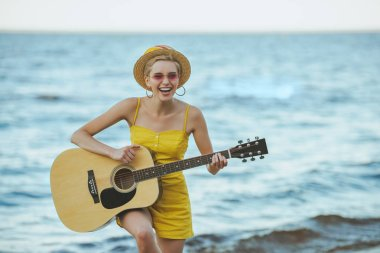portrait of happy young woman playing guitar with sea on background