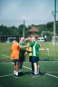 Fotografie interracial elderly football players after match on green field