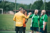 Fényképek interracial elderly football players shaking hands after match on green field