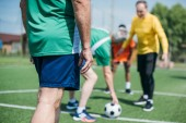 Fotografie partial view of multicultural elderly friends playing football together