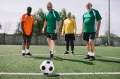 Fotografie Selektivní fokus fotbalový míč a multikulturní starších mužů na zelené fotbalové hřiště