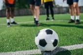 Selektivní fokus fotbalový míč a multikulturní starších mužů na zelené fotbalové hřiště
