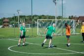 Fotografie multikulturní starších přátel spolu hrají fotbal