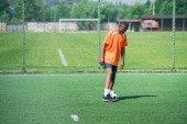 african american elderly man training with football ball in field