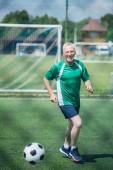 Fotografie fröhliche Greis Fußballspielen auf Feld an Sommertag