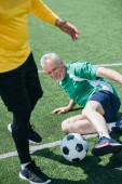 Fotografie partial view of elderly men playing football on field