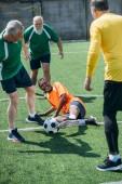 Fotografie s úsměvem multikulturní starší přátelé spolu hrají fotbal