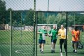 Fotografie Skupina interracial starších sportovců sportovní láhve s vodou na fotbalové hřiště