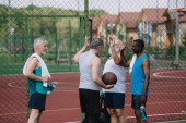 Fotografia gruppo di sportivi vecchi multirazziali con sfera di pallacanestro dando cinque alto a vicenda sul campo da giuoco