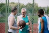 Fotografia gruppo di sportivi vecchi multirazziali con sfera di pallacanestro sul campo da giuoco