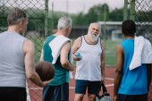 Photo selective focus of group of multiracial old sportsmen with basketball ball on playground