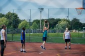 Fotografie Interracial ältere Sportler spielen Basketball auf Spielplatz
