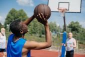 Fotografie gemischtrassig ältere Männer zusammen zu spielen Basketball auf Spielplatz an Sommertag
