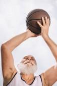 Fotografie niedrigen Winkel Ansicht von älteren bärtigen Mann mit Basketball Ball in Hand