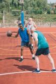 Fotografie mnohonárodnostní starších mužů společně hrát basketbal na hřišti v letním dni