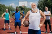 Fotografie selective focus of multiethnic elderly sportsmen with basketball ball on playground