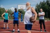 Fotografia messa a fuoco selettiva degli sportsmen multietnico anziani con sfera di pallacanestro sul campo da giuoco