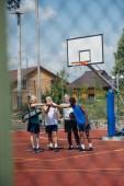 Fotografia sportsmen anziani multietnici con sfera di pallacanestro sul campo da giuoco
