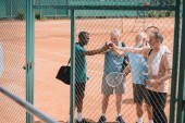 Fotografie multicultural group of elderly tennis players holding hands together after game on court
