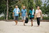Fotografie multiethnic elderly volleyball players with sportive water bottles walking on beach after game