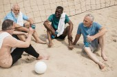 multiethnic smiling elderly volleyball players with sportive water bottles resting after game