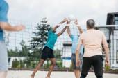 částečný pohled multikulturní staří přátelé hrát volejbal na pláži v letním dni