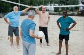 multikulturní staří přátelé hrát volejbal na pláži v letním dni