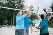 Photo smiling multiethnic old volleyball players giving high five to each other after game