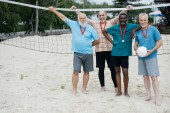 Fotografie smiling interracial elderly volleyball players with medals standing on sandy beach
