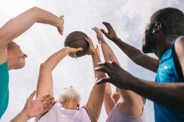 low angle view of interracial elderly sportsmen playing basketball together
