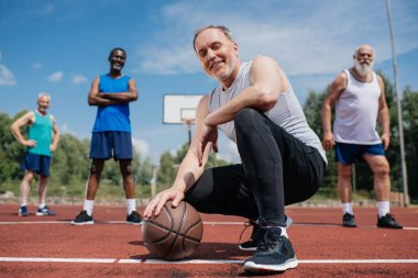 selective focus of multiethnic elderly sportsmen with basketball ball on playground