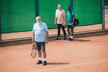 Multiracial elderly men standing on tennis court stock vector