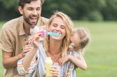 Fotografie happy family with one child hugging and blowing soap bubbles in park