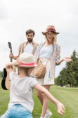 beautiful mother and happy father with acoustic guitar looking at cute little daughter having fun in park