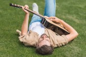 Fotografie mladý muž ležící na trávě a hrál na akustickou kytaru
