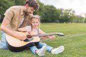 Šťastný otec a dcera hraje na akustickou kytaru v parku