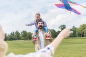 Fotografie Oříznout záběr šťastná rodina s jedním dítětem hrát s barevnými draka v parku