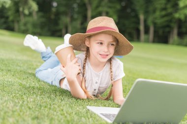 Happy child holding paper cup and using laptop while lying on grass in park stock vector