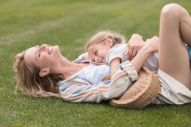 happy mother and daughter hugging while lying on green grass in park