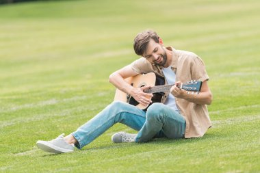 smiling young man sitting on lawn and playing acoustic guitar