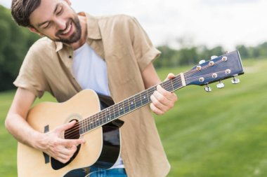 happy young man playing acoustic guitar in park