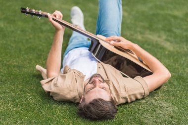 young man lying on grass and playing acoustic guitar