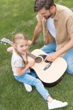 overhead view of father and daughter playing acoustic guitar in park