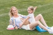Fotografie šťastný matka a dcera objímat a baví spolu na zeleném trávníku