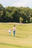 Fotografie zadní pohled na otce a dceru běží na louku a hrát si s kite