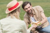 happy young couple holding sandwiches while spending time together at picnic